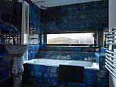 Badezimmer mit Landschaftsblick durch liegendes Fenster zwischen kräftig blau geflammten Fliesen
