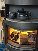 Blue-glazed ceramic teacup and teapot on warming plate of wood-burning stove with roaring fire