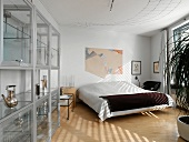 Bedroom with simple double bed and modern glass display case