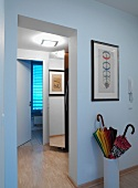 Illuminated hallway in contemporary apartment with framed pictured and umbrella stand