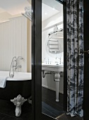 Black and white, retro bathroom with pedestal washstand, claw-footed bathtub and wood-panelled walls