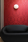 Black designer sofa in front of red wallpaper with traditional, floral pattern