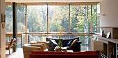 Solarhaus am Hang - Sitzecke am Kamin mit Blick in Baumwipfel