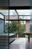 Modern bathroom in solar house with view of sky and trees through glass wall with sliding element and glass roof