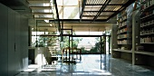 Contemporary solar house building - airy staircase to gallery with sun from above and dining area in front of wide glass wall