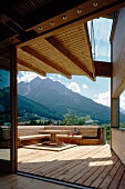 Sunny, partially roofed wooden terrace with generous corner bench and view of mountains