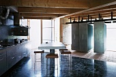 Kitchen unit and dining area with concrete table next to suspended, moveable cupboards in contemporary wooden house