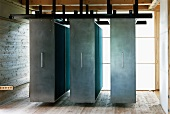 Suspended, moveable cupboards with steel doors in front of translucent walls in contemporary house