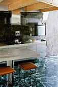 Concrete tops on kitchen unit and dining table, black and white stone tiles and black marbled back wall in modern wooden house