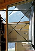 View of bathroom through steel struts on window of modern wooden house with view of mountains