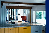 View of dining area with fifties chairs across modern kitchen unit with colourful wooden fronts and granite counter