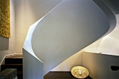 Sculptural spiral staircase with white, masonry balustrade, artwork with text motif and egg-shaped floor lamp