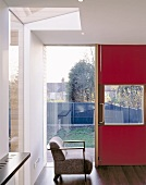 Red, modern front door with large windows and retro armchair