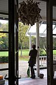 Blick in den Garten mit Herbststimmung - Frau auf Terrasse eines Landhauses