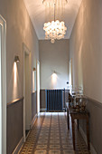 Hallway in period apartment lit by modern sconce lamps and ceiling lamp made from glass spheres