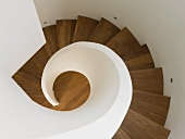 Top view of wooden spiral staircase with white balustrade