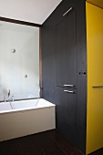 Bathtub, black fitted cupboard & yellow niche