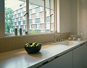 White kitchen unit with window & view of apartment building front