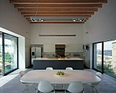Modern kitchen-dining room with wooden beams on ceiling and large windows on both side walls