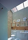 A light bathroom with a brick wall, framed photos and a large skylight