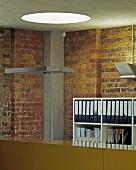 Büro mit rundem Oberlicht, rustikaler Ziegelwand und Betondecke