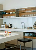 A modern kitchen with a crockery shelf and a bar with a bar stool