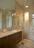 A bathroom with marble tiles and a glass partition wall separating the shower area