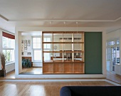 Spacious, modern kitchen-dining room with wooden partition with integrated shelving and serving hatch
