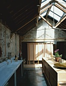 Open-plan kitchen in room with wood & glass roof structure