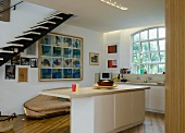 Open-plan kitchen with central island, sofa & floating staircase
