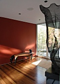 Living space with red wall, seating & sculpture