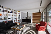 Patterns of light and shade in spacious, bright living room with extensive bookcase and striped sliding door