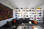 Modernes Wohnzimmer mit schwarzer Eckcouch; dahinter eine breite, weisse Bücherwand und ein großes Gemälde