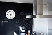 Station clock hanging on black wall with lettering above kitchen island