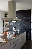 Kitchen island with extractor hood in modern kitchen with floor-to-ceiling black slate panel on wall in background