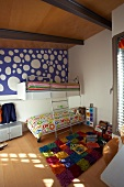 Cheerful children's bedroom in attic with colourful, chequered rug and blue wallpaper with large white spots