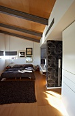 Attic bedroom with seventies' wall design, large double bed and narrow, horizontal windows
