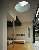 Stylish living space in house with window slits in wall and circular skylight in ceiling