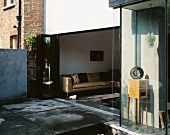 Terrace in front of living room with open folding door and view of sofa