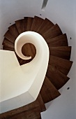 View of spiral stairwell with wooden treads and solid, white balustrade