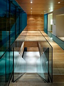 Contemporary building with glass wall in wood-clad hallway and view down staircase