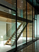 Glass wall of contemporary house with view of illuminated stairwell