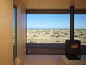 Free-standing, wood-burning stove in front of floor-to-ceiling windows with sea view