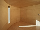 Empty room with curved wall and wood-clad walls, ceiling and floor