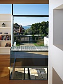 Glass balustrade around aperture in floor in front of floor-to-ceiling windows with superb view