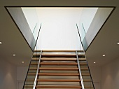 Modern staircase with wooden treads and glass balustrade