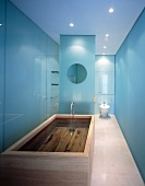 Designer bathroom with filled wooden bathtub