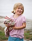 Girl carrying picnic blanket