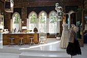 Freistehender grosser Küchenblock und Modepuppen mit festlichen Kleidern in Backsteinloft mit Kirchenfenstern