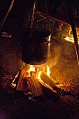 Mulled wine warming over bonfire